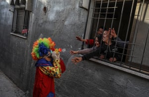 A Palestinian clown wears a protective face mask while entertaining children staying in their home due to the precautionary measures.