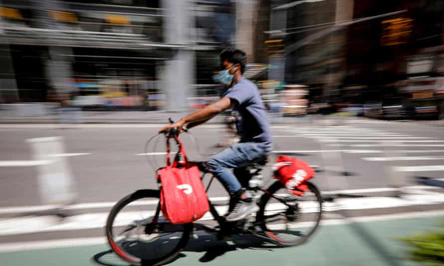 A rider for Grubhub food delivery service rides a bicycle during a delivery in midtown Manhattan, New York.