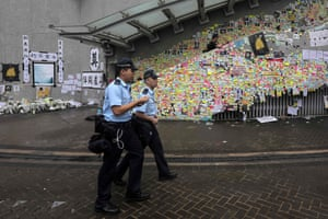 Police walk past posters and notes left by protesters.