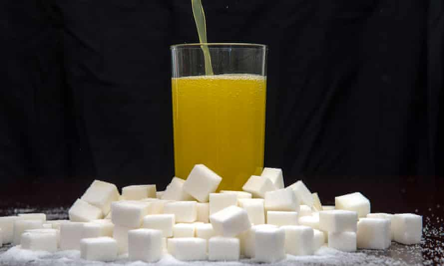 An orange carbonated drink surrounded by sugar cubes.