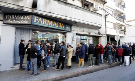 Uruguayans queue in line outside of a pharmacy to buy legal marijuana in Montevideo
