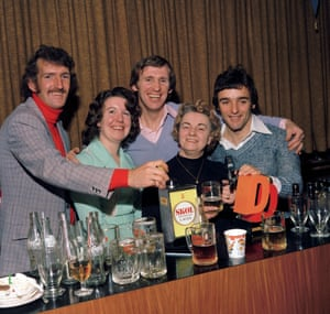 Manchester United's Alex Stepney, left, Pat Crerand and Lou Macari, right, help out behind the bar during the club's 1976 Christmas party at Old Trafford
