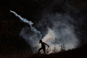 A Palestinian demonstrator returns a teargas canister fired by Israeli troops during a protest against Jewish settlements and normalising ties with Israel at Asira al-Qibliya in the Israeli-occupied West Bank.