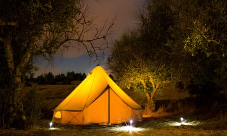 A tent is seen lit up in the countryside.