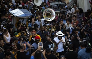 Passersby join in the conga as trumpet, trombone and saxophone players march through the streets
