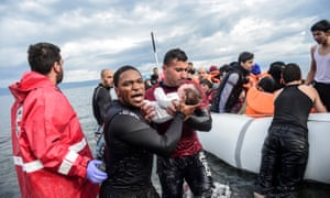 Rescuers help refugee families on Lesbos.