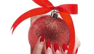 Shiny red bauble with red bow on top, held by red-nailed hand