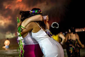 Women hug on Copacabana beach in Rio de Janeiro, Brazil, as fireworks go off for the New Year.