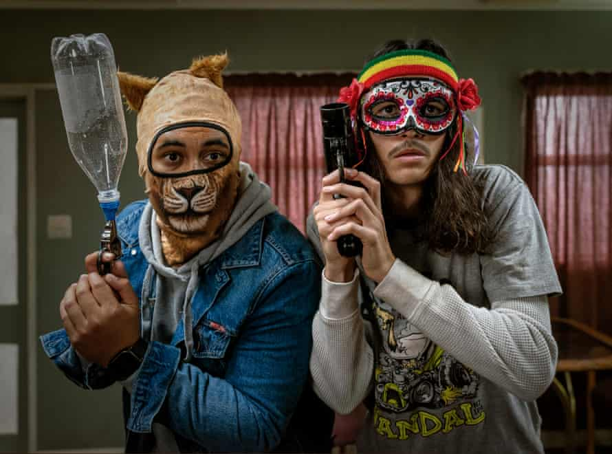 Two young men in comical masks holding guns