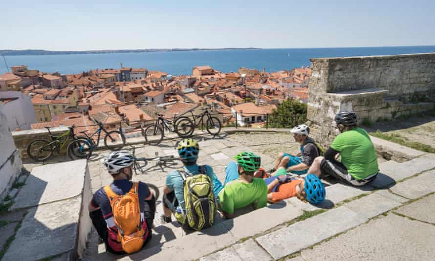 Bikers sitting on steps above Piran and the Adriatic