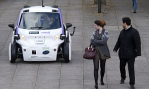 People look towards an autonomous self-driving vehicle, as it is tested in a pedestrianised zone, during a media event in Milton Keynes