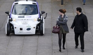 Two pedestrians look round at a driverless car behind them