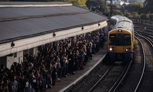 Commuters wait to board a train at Clapham Junction station.
