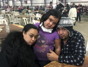 Marolyn Romero-Sim and Hugo Romero-Rodriguez with their nine-year-old daughter Milagros wait at an evacuation centre at the Ventura County Fairgrounds after their RV was destroyed by fire