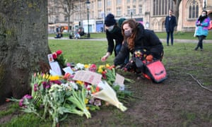 People place flowers at a tree on College Green in Bristol after the Reclaim These Streets vigil for Sarah Everard was officially cancelled.