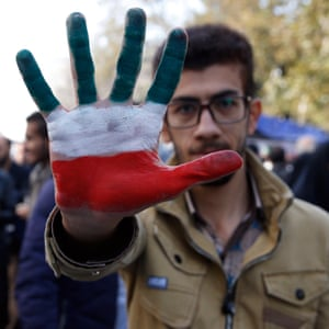 An Iranian man shows his hand painted with Iran's national flag colours during the anti-US demonstration.