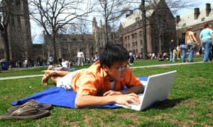 ADBNNR Yale Student works on a computer on campus outdoors during a warm spring day