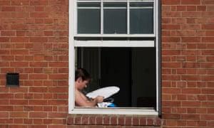 A man using a homemade sun reflector in London.