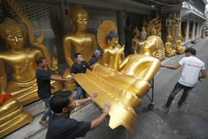 Bangkok, Thailand: Shop workers remove a Buddha statue in preparation for the upcoming Buddhist Lent.