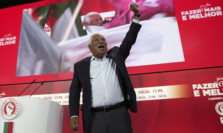 António Costa raises his fist in air in front of podium and large TV screen at rally