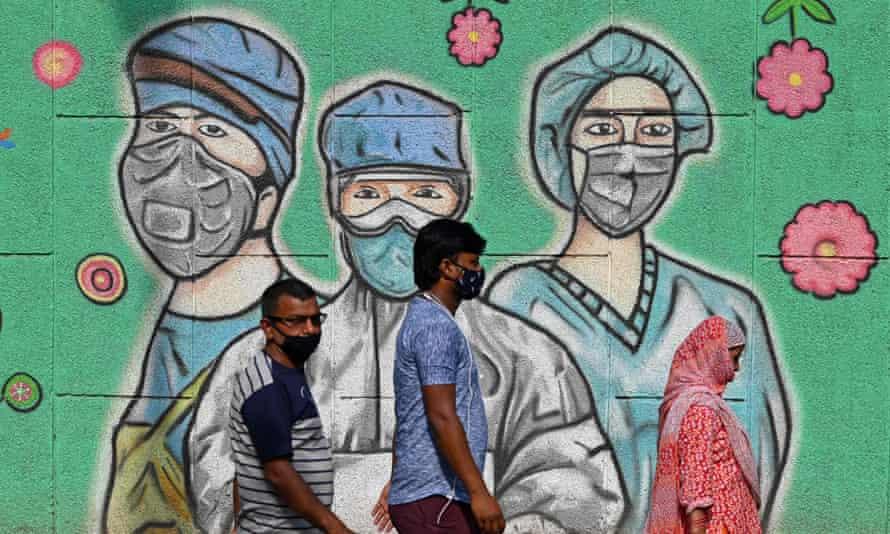 Commuters in Delhi pass a mural depicting masked medics