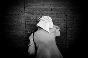 """One of the """"Madres de Plaza de Mayo"""" (Mothers of May Square) cries on her son's name inscribed on the wall of the Memorial Park in Buenos Aires. They meet every Thursday to commemorate their sons, and protest against the economic and political situation in Argentina"""