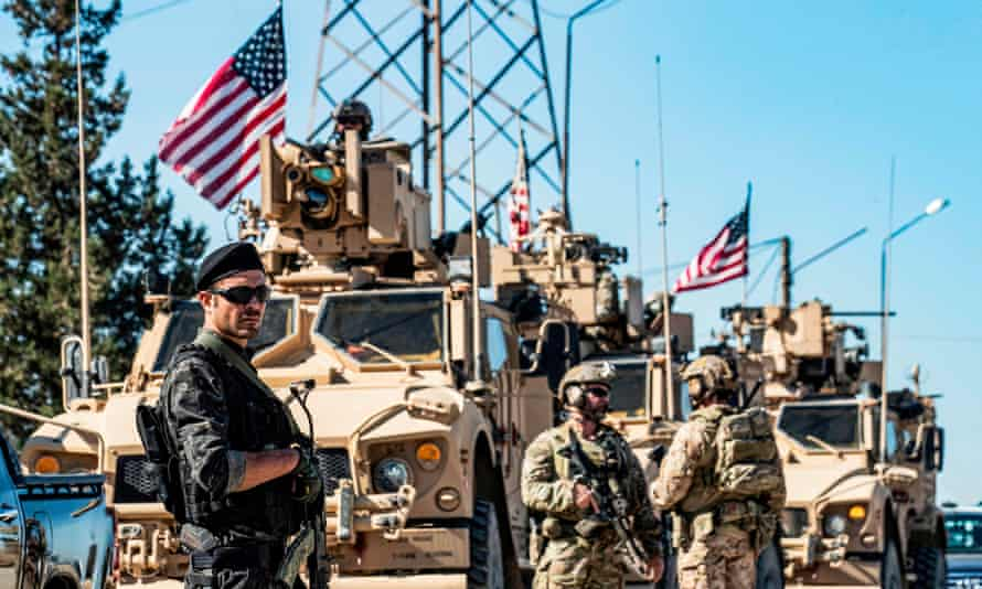 A member of the Kurdish People's Protection Units (YPG) stands guard as US military armoured vehicles and soldiers patrol near an oil well in Syria's northeastern Hasakeh province.