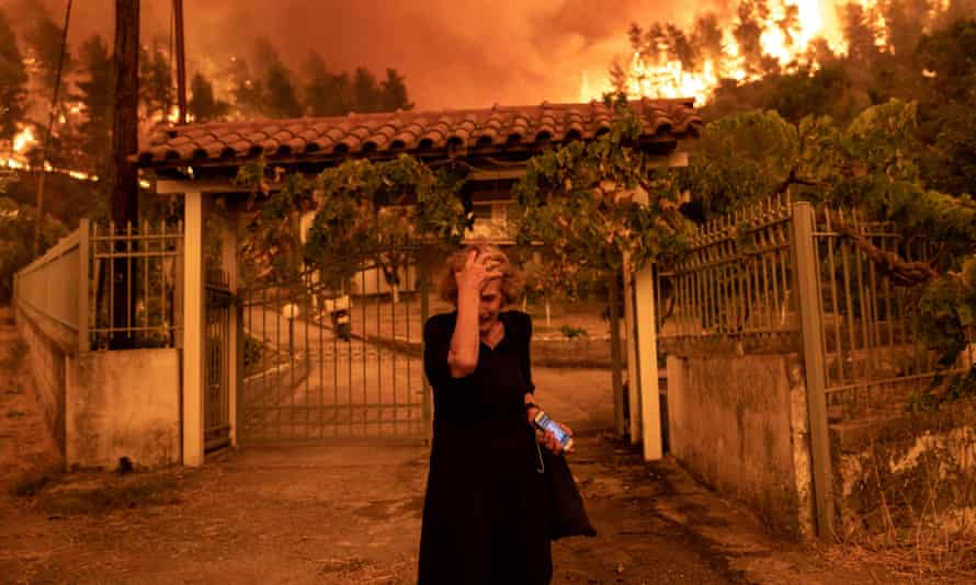 A woman holds her hand to her head as wildfire approaches her house in Evia, Greece.