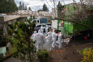 A cleaning crew wearing protective clothing (PPE) to protect them from coronavirus prepares to enter the Life Care Center on March 12, 2020 in Kirkland, Washington. The nursing home in the Seattle suburbs has had the most deaths due to COVID-19 of anywhere in the United States.
