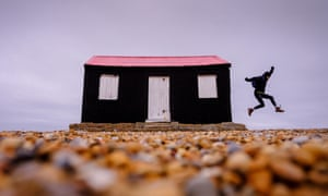 A woman leaps from the side of a small black and red hut on the riverbank in Rye Harbour Nature Reserve, East Sussex UK