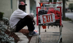 A homeless man sits next to a shopping cart as the spread of Covid-19 continues, in New Orleans, Louisiana, last week.
