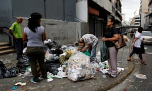 People search through garbage in Caracas, Venezuela, on Tuesday.