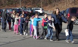 In this photo provided by the Newtown Bee, Connecticut state police lead children from the Sandy Hook elementary school following a shooting there in 2012.