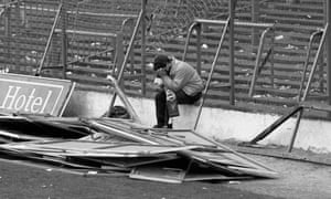 A Liverpool fan sits in the empty Hillsborough stadium on 15 April 1989 following the disaster which killed 96 people