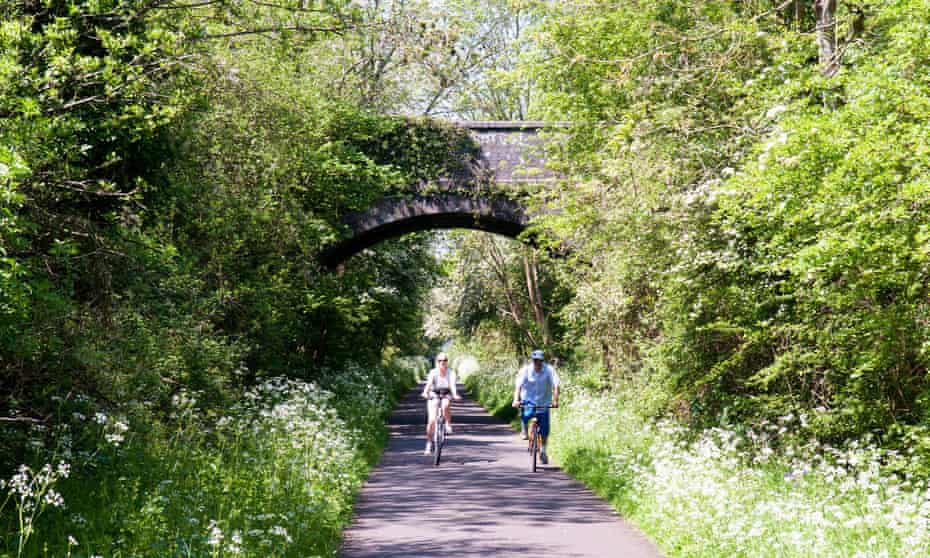 A couple cycling on the Bristol and Bath Railway Path in spring.