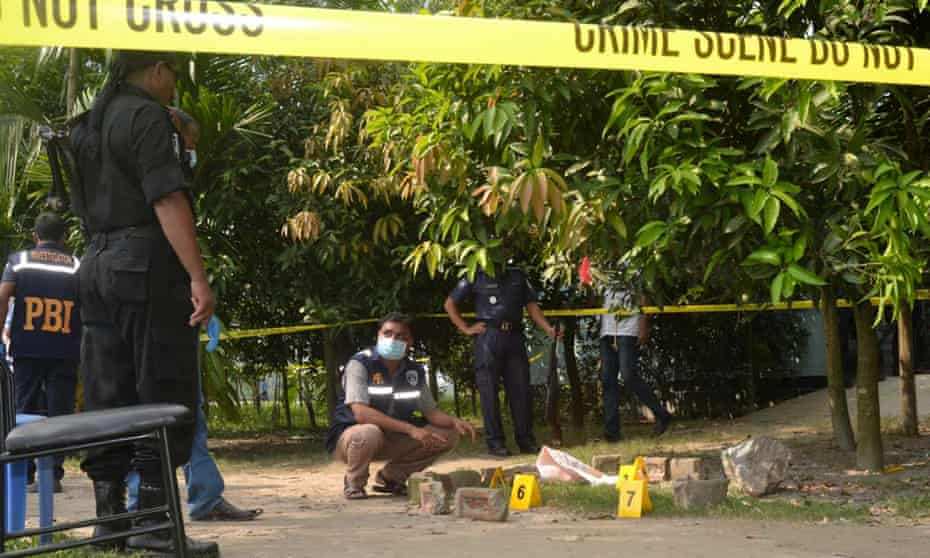 Bangladeshi security officers examine the site where Kunio Hoshi was killed in Rangpur.