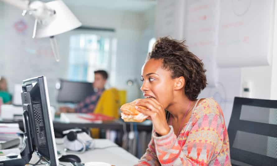 Businesswoman eating burger at desk.