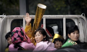 North Koreans riding on the back of a pickup truck carry props to be used during upcoming anniversary celebrations.