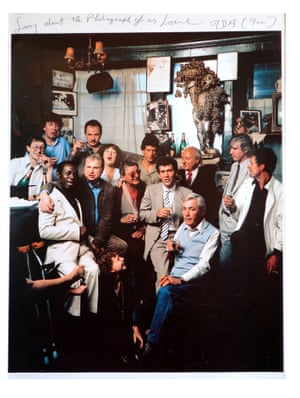 A club photograph taken in the 1980s. The two figures on the far left are Michael Wojas, the club's third and final proprietor, and the actor Tom Baker. Francis Bacon sits on the stool with his arm around an unknown man and to his right is Jeffrey Bernard, the journalist and author of the Spectator's Low Life column