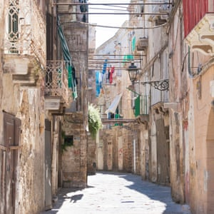 Narrow street with washing lines between buildings, Taranto, Italy.