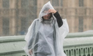 A pedestrian caught in heavy downpours on Westminster Bridge in central London