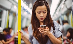 Young lady using smartphone on train