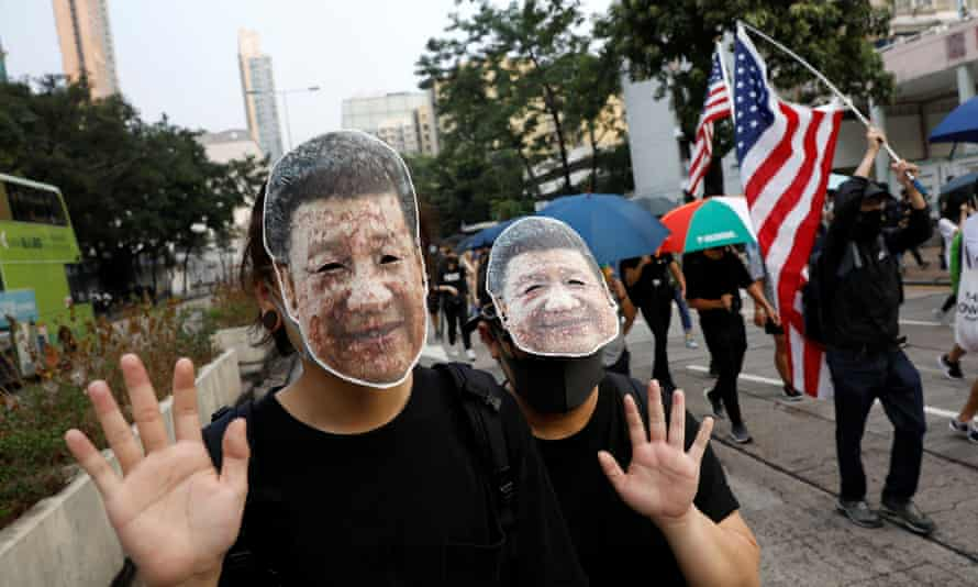 Anti-government protesters wear masks bearing the image of the Chinese president, Xi Jinping, in Hong Kong