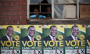 Children look through a window above election posters of Emmerson Mnangagwa