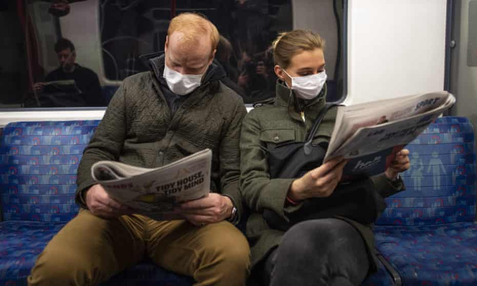People reading newspapers on the London Underground, March 2020