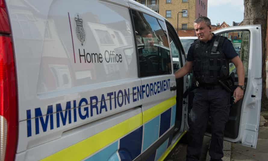 An immigration enforcement officer during a raid on a home in London.