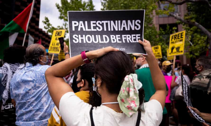 A person holds a poster reading 'Palestinians should be free' during a demonstration in front of the consulate general of Israel in Los Angeles, California, on 11 May.