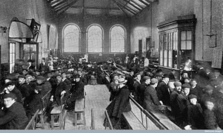 Old, black and white photo shows a large, square room filled with wooden benches.  Dozens of people, mostly men, sit and wait.
