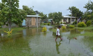Fijian girl walks over flooded land in her village.