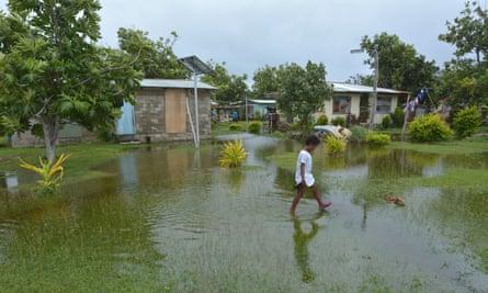 Fijian girl walks over flooded land in her village.